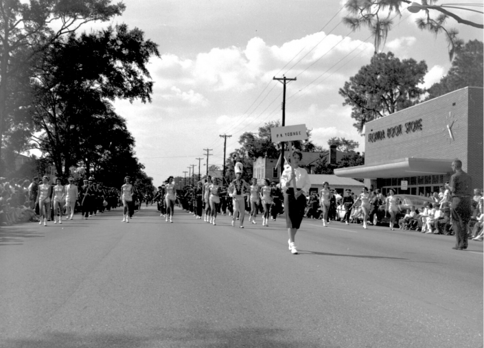 1961 - P.K. Yonge Marching Band in the Homecoming Parade - Girl holding a sign with twirlers behind her