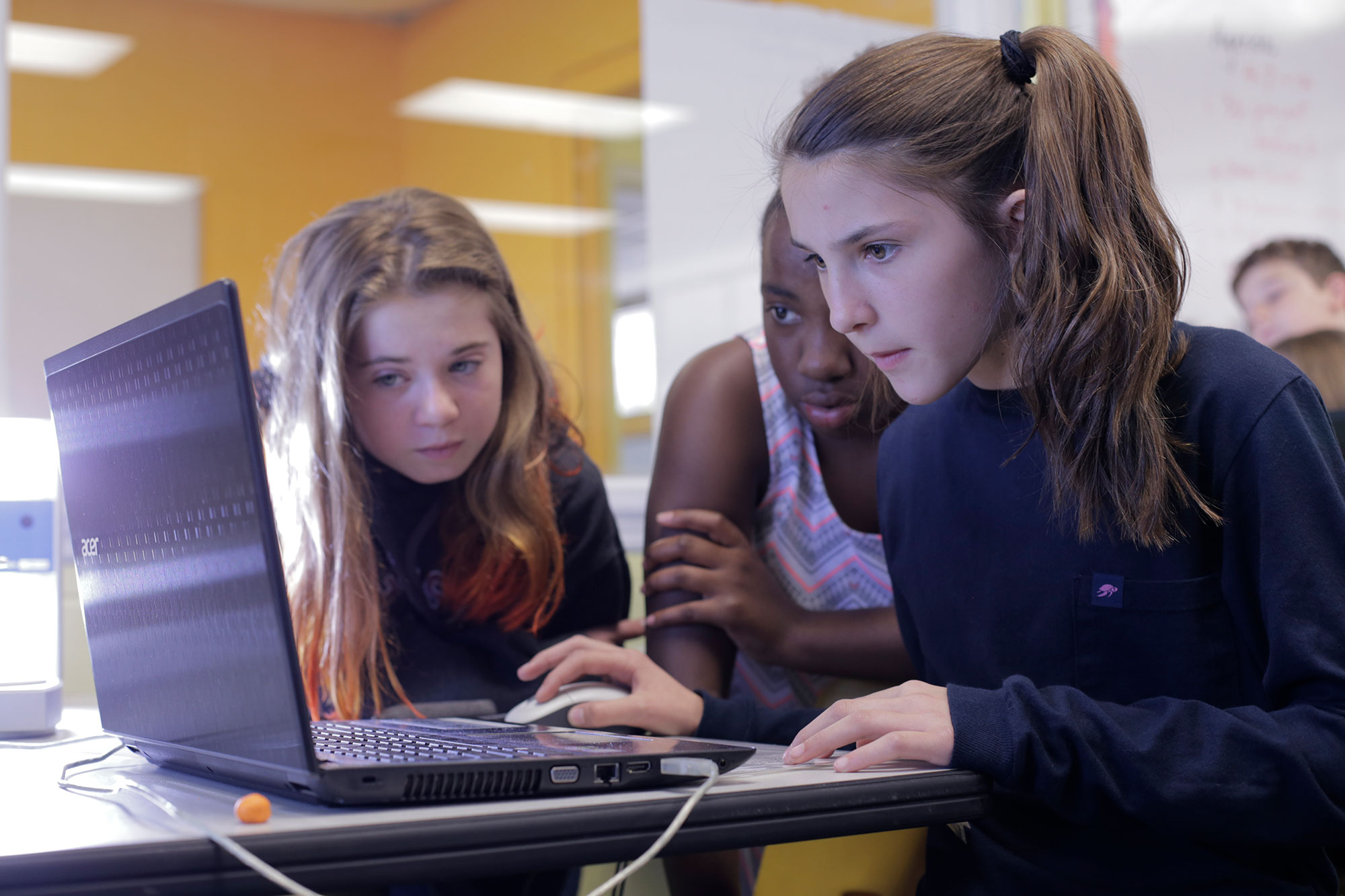 Three students look at a computer for developing a 3D model of a Megalodon tooth.