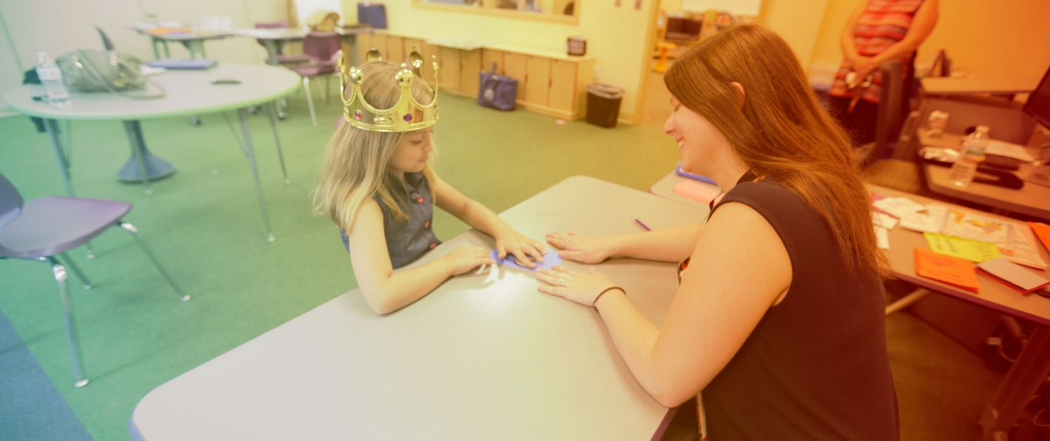 A girl wearing a crown sounds out letters with her graduate student teacher.