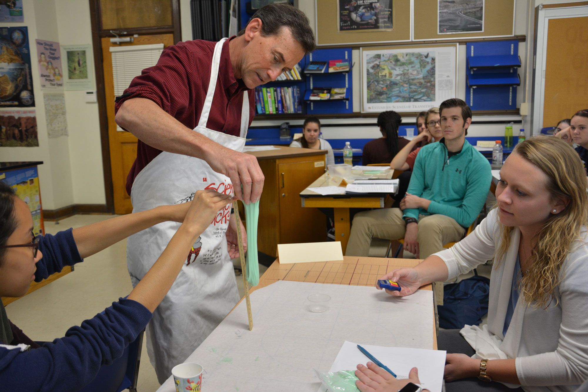 Griff Jones stretching silly putty while a student measures the length of the stretch with a ruler in a classroom.