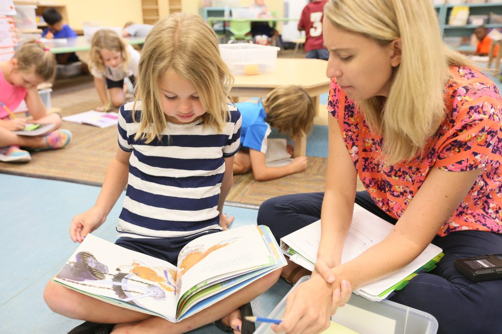 Little girl reading with a teacher.