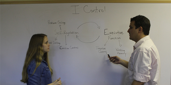 Two research assistants working on a whiteboard