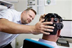 Pasha Antonenko adjusting the EEG headgear of a study subject