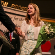 Lauren Marlowe shaking hands while accepting teacher of the year award