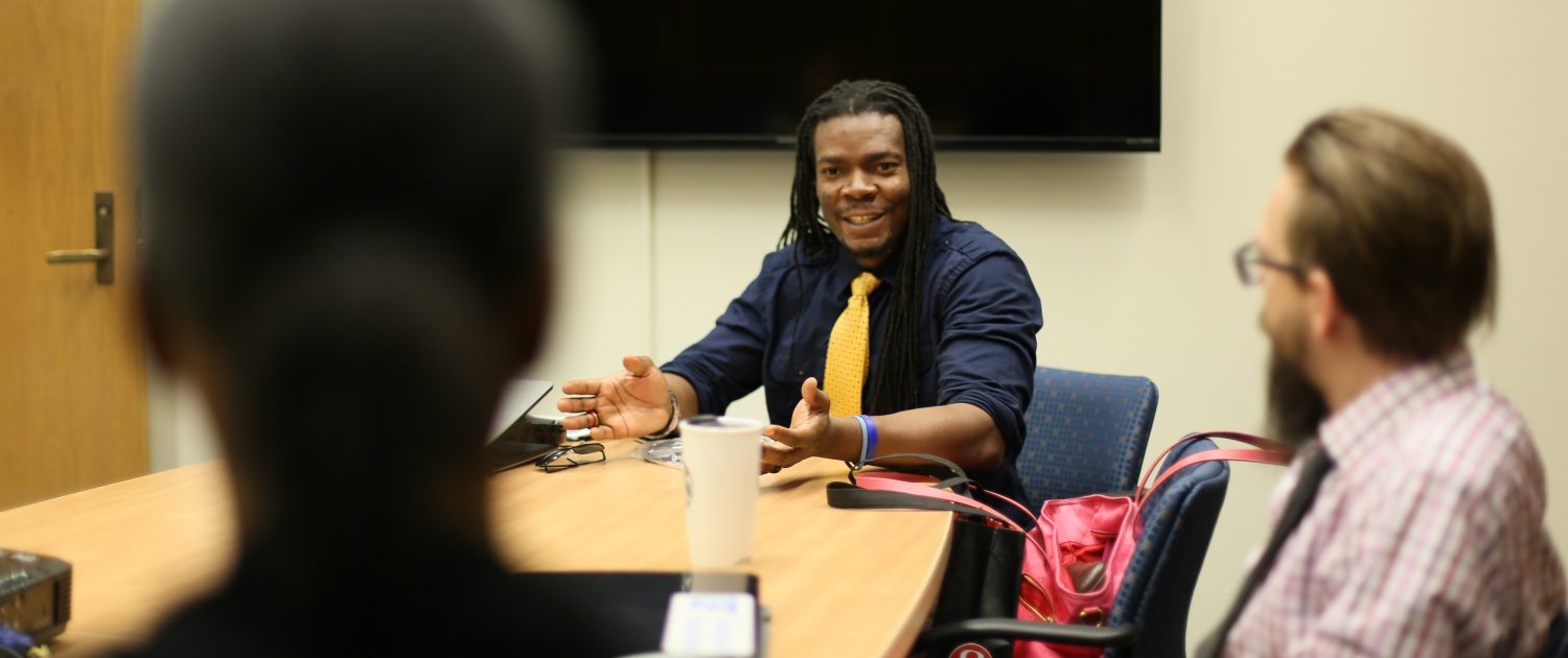 Jonte Myers speaking to a group of people at a conference table.