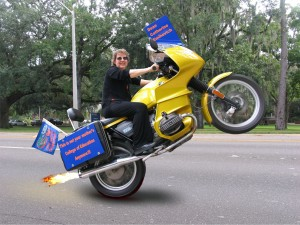 Dean Catherine Emihovich pops wheelie on motorcycle (with some help from Photoshop) in preparation for ride in 2005 Homecoming parade.