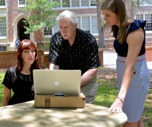 Professor Smith picks a shady spot on the front lawn of Norman Hall to review a spreadsheet with second-year doctoral students Michelle Cumming and Kristin Merrill.