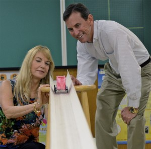 COE professors Linda and Griff Jones send a hand-made paper test car down a race track Griff Jones designed using sections of a plastic rain gutter.