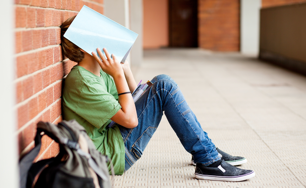 Stressed student with head in book