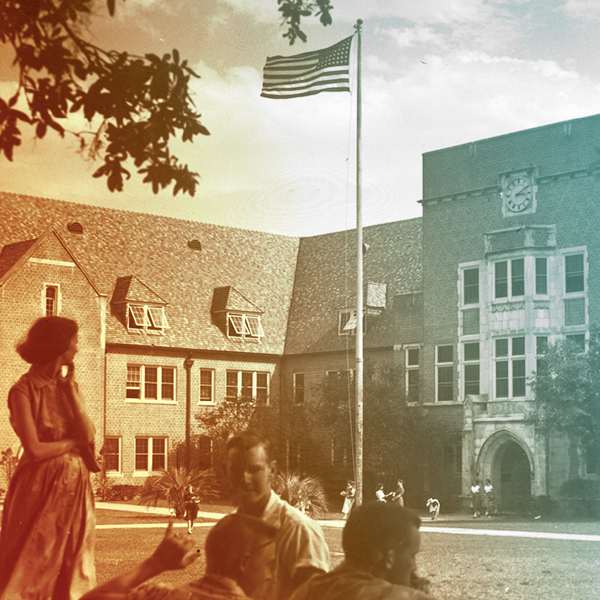 A woman staring at old Norman Hall while a flag billows in the background.